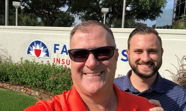 Two men in front of a Farmers Insurance sign
