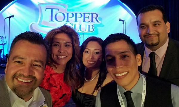 Five people taking a photo in front of a Topper Club sign.