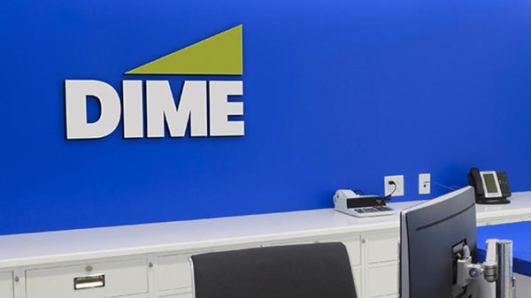 The background of a Dime desk area where the Dime Logo sits in front of a royal blue background and above a white shelving unit and the tops of a computer monitor and computer chair can be seen.