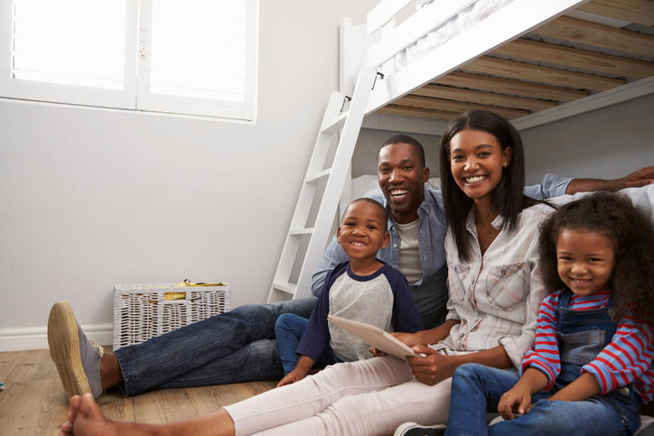 smiling family sitting in front of bunk beds