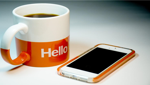 A cup of coffee and a cell phone