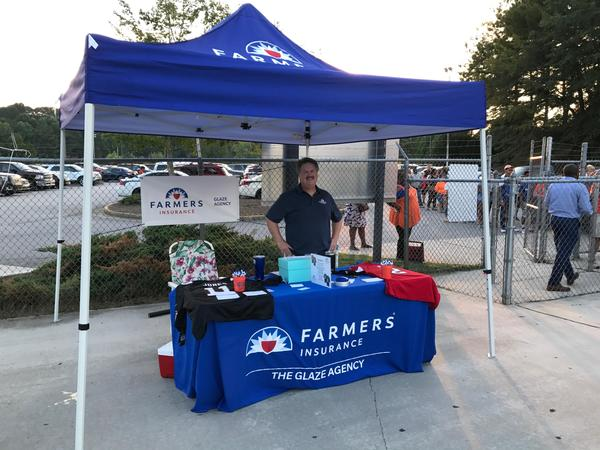Farmers Insurance table and tent set up outside a football game for The Glaze Agency