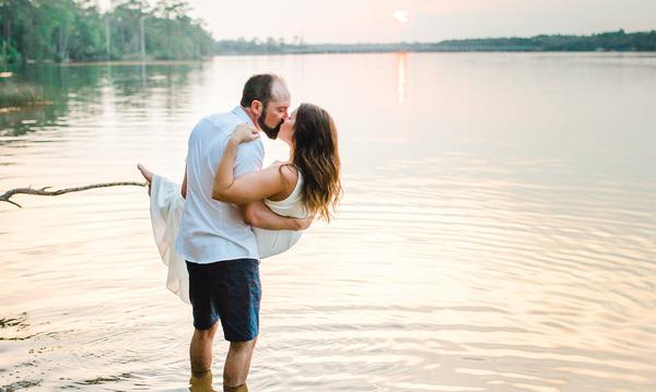 Man holding wife in arms by a lake.