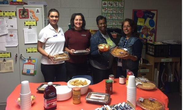 4 female staff members serving lunch to great teachers.