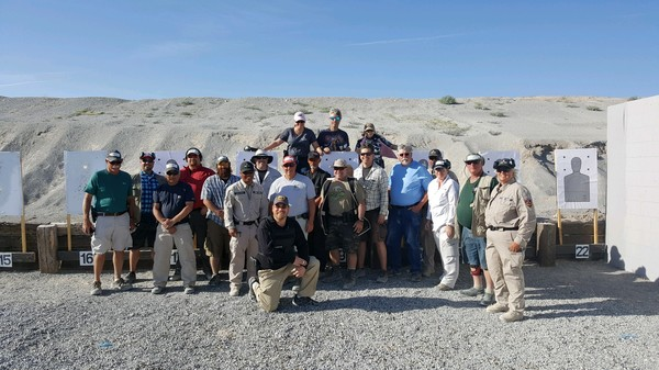 Photo of group of people in front of a mountain at a shooting range
