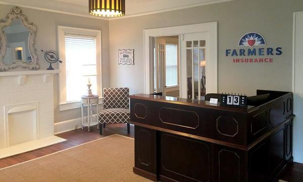 office interior with reception area, chair in the corner and farmers logo on the wall.