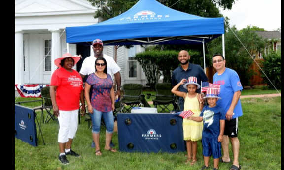 Agent Genaro Mendez standing with family and friends next to a branded Farmers Insurance promotional booth.