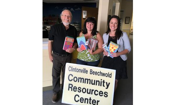 The agent poses with two women - they are holding books and standing behind a sign that reads Community Resources Center