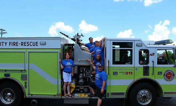 Six adults posing for a photo in a Fire truck.