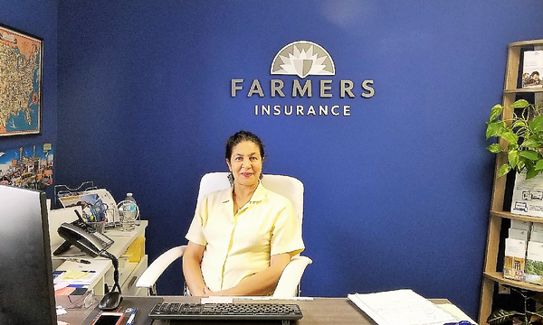 Irene Morgan Agency staff member sitting behind her desk, with the Farmers logo in the background.