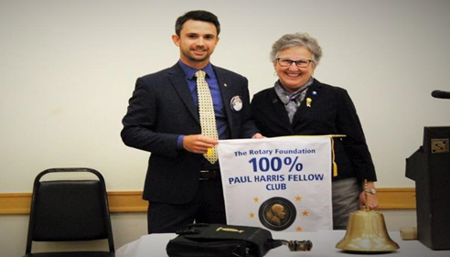 Cody Barton, President of Purcell Rotary Club, Receives 100% Paul Harris Banner.