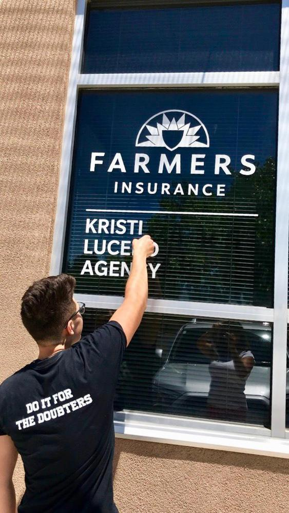 Man creating a Farmers Insurance sign