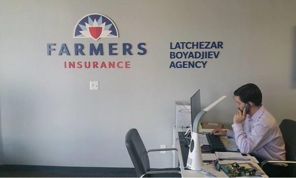 A man sits at his desk at a Farmers Insurance office and dials the phone