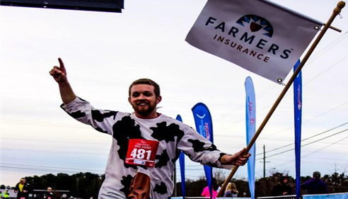 Agent running in a race holding a Farmers flag