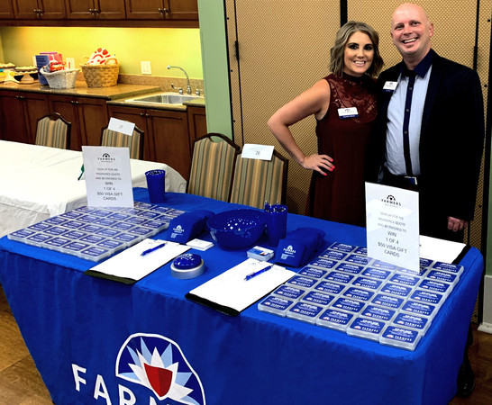 Two people smiling behind Farmers Insurance booth
