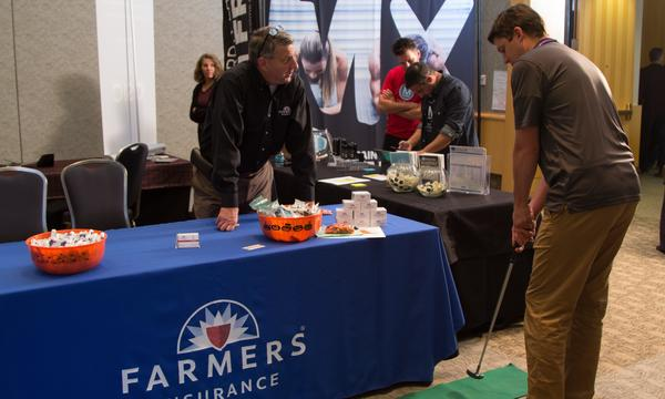 Agent standing behind a farmers booth while a man stands with a golf putter