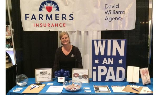 Staff member standing at a Farmers table at an expo.