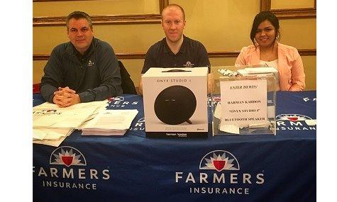 Three adults sitting at a Farmers Insurance table.