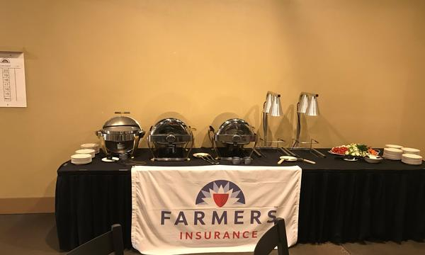 The Farmers Insurance logo on a table with buffet style trays and plates on it.