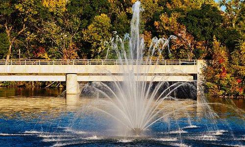 A water fountain with a bridge and autumn foliage in the background.