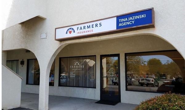 Storefront view - Farmers Insurance Tina Jazinski Agency sign above glass door and large windows.