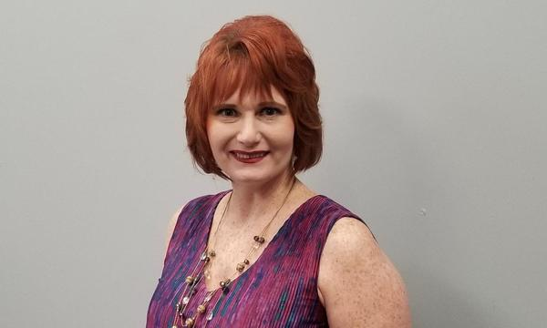 Michael Benham Agency staff member, Ronda Anderson, in a purple dress on a gray wall.