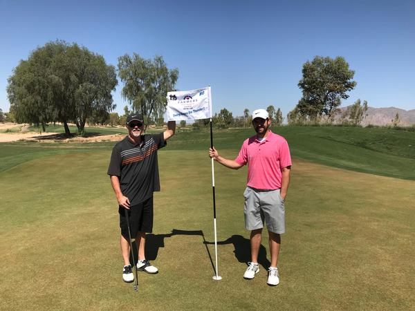 two men holding a Farmers Flag on a golf course