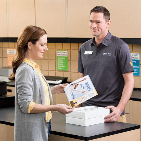 Customer receiving print handout from employee