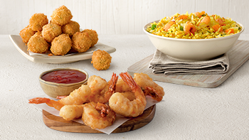 Fish pops, Sriracha Pop Prawns and shrimp fried rice arranged on a white table.