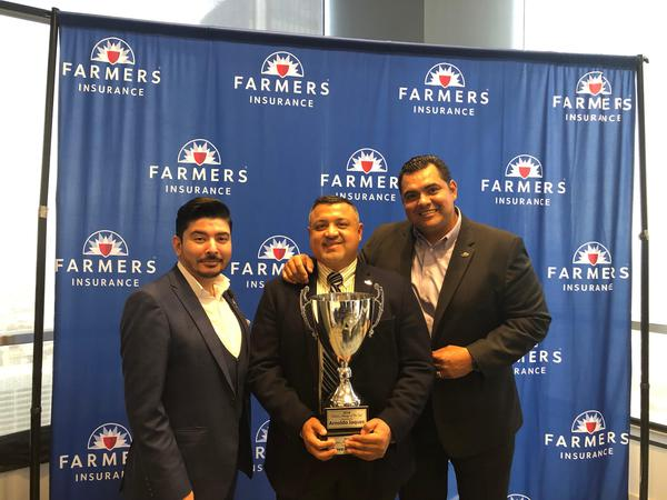 Three agents holding a trophy