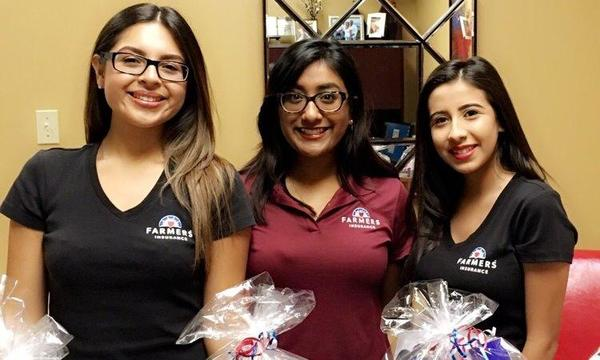 Three women wearing Farmers Insurance shirts standing together holding gift baskets.