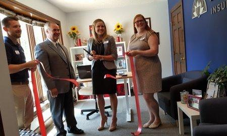 Agent Jenna cutting a ribbon for grand opening of new office.
