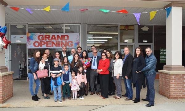 A group of people stand in front of a store Grand Opening