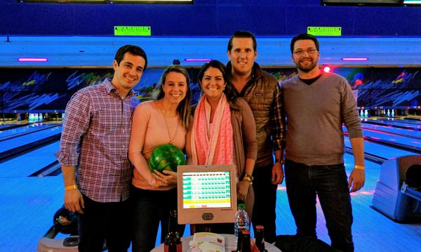 Agent Christopher with 2 women and 2 men in front of a bowling alley lane.