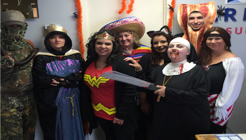 Agent and staff standing dressed in Halloween costumes