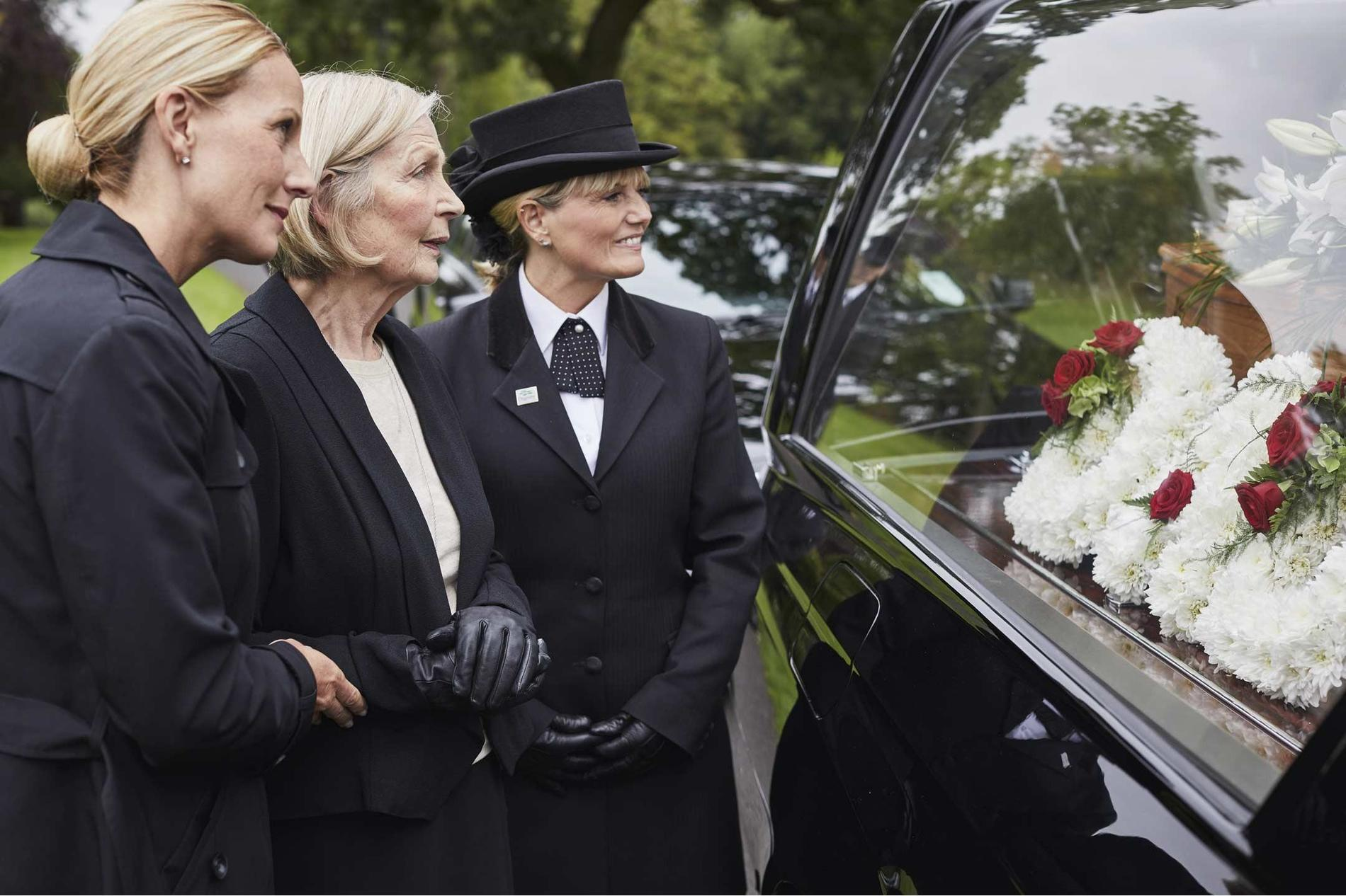 Funeral directors with two mourners at a full service funeral | Dignity Funerals