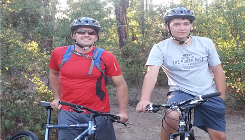 Two men riding bikes and smiling at the camera