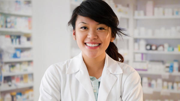 Pharmacist smiling in front of the pharmacy