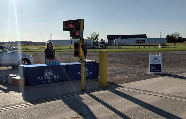 Woman standing in behind Farmers Insurance booth