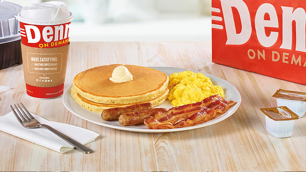 To-go cup of Denny's Coffee, a white plate containing a stack of pancakes with a dollop of butter, two sausage links, two slices of bacon and scrambled eggs, two to-go containers of syrup.