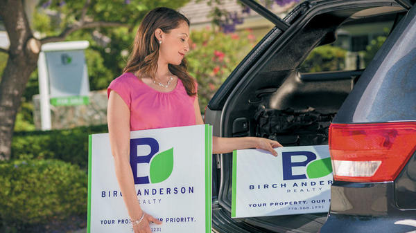 Female loading lawn signs into trunk of car