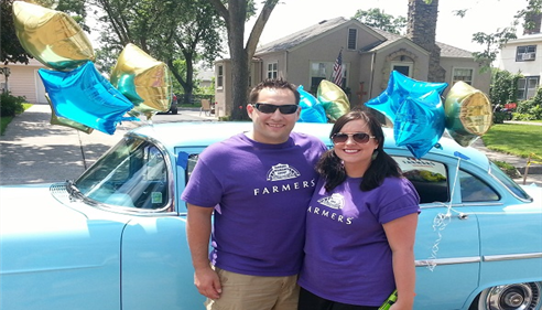Agent posing with a man, both wearing purple Farmers insurance t-shirts