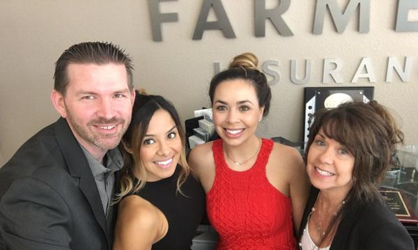 Agent and staff members pose in front of Farmers sign.