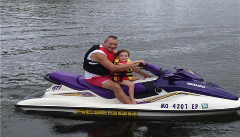 Agent on jet ski with grandchild.