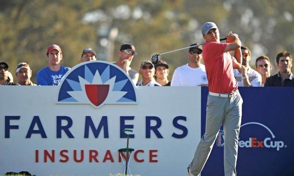 Golfer finishing his swing in front of a Farmers Insurance sign
