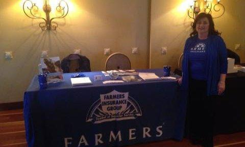 Agent standing in front of a Farmers booth at a conference