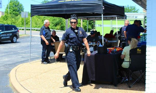A photo of a police officer walking around a local BBQ celebration.