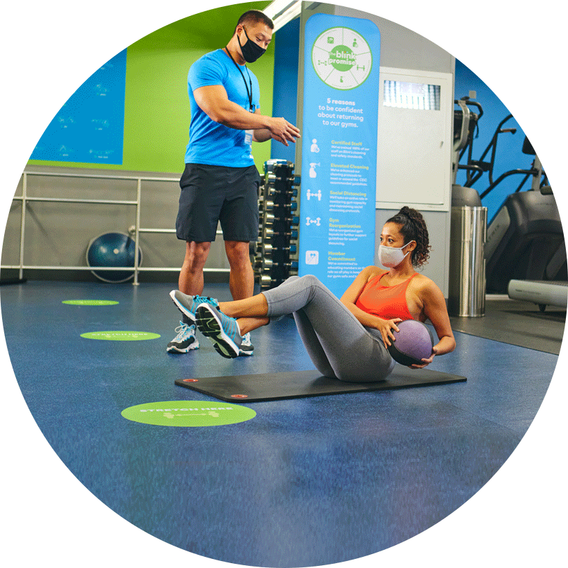 personal trainer coaching a client in the gym. The client is female and sitting on a mat doing ab exercises.
