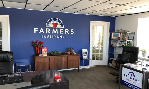 A blue wall with the Farmers Insurance logo, inside of Agent Joyce Felder's office.