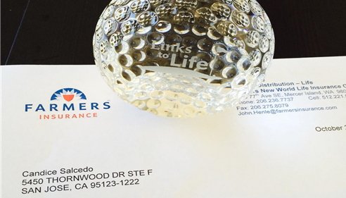 A glass golf ball award placed on top of an envelope